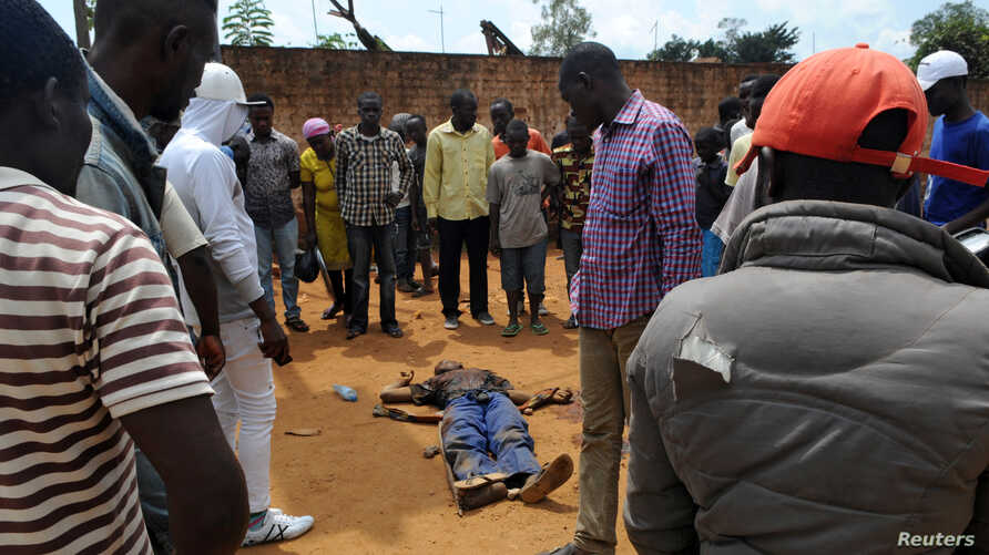 Civilians gather to look at the dead body of an unidentified man killed during fighting between the army and militia fighters in Beni, eastern Democratic Republic of the Congo, June 22, 2017.