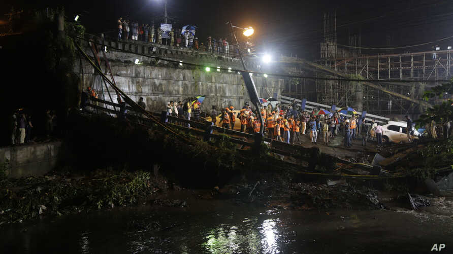 Rescuers work at the scene after a highway overpass collapsed on a sewage canal in Kolkata, India, Tuesday, Sept. 4, 2018.