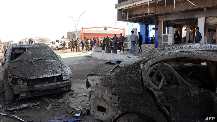 Iraqis gather at the site of a car bomb in Mosul, Iraq, Nov. 9, 2018. The previous night's explosion killed three people, the first such attack since jihadists were ousted from the city last year.