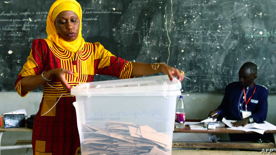 An electoral worker opens a ballot box following the closure of polling stations at the end of Senegal's general election, on July 30, 2017 in Dakar.