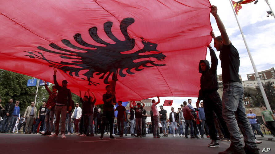 Ethnic Albanians hold a large Albanian flag, during a protest by ethnic Albanian civic organizations and several minor political parties in front of the parliament building in Skopje, Macedonia, demanding the establishment of the rule of law, April 2