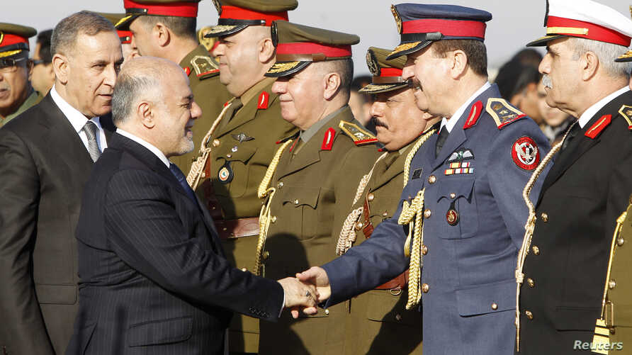 Iraqi Prime Minister Haider al-Abadi, second from left, shakes hands with military officials with Iraq Defense Minister Khaled al-Obeidi, left, during the Iraqi Army Day anniversary celebration, in Baghdad, Jan. 6, 2015.