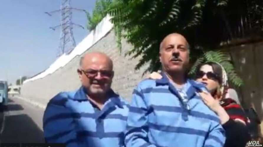 Screen grab of a mobile phone video of Iranian ex-lawmaker Ghasem Sholesadi (right) and fellow lawyer Arash Keikhosravi being led in handcuffs and shackles to Tehran's Evin prison complex for a meeting with prosecutors on Aug. 21, 2018, after their a