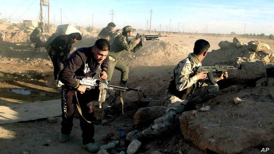 Iraqi security forces take combat positions on the front line with Islamic State group militants in Ramadi, capital of Iraq's Anbar province, 115 kilometers (70 miles) west of Baghdad, Dec. 10, 2015.