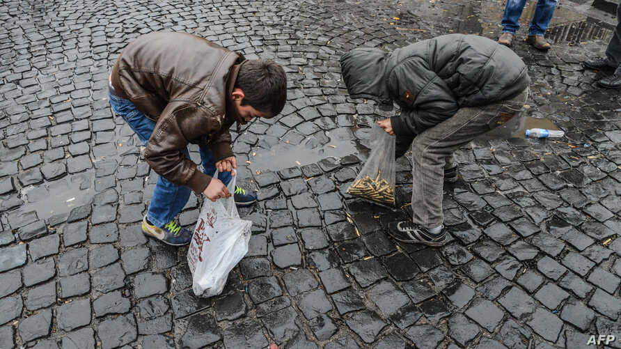 Children collect bullet shells off the streets of  Sur district, on December 30, 2015 in the mainly Kurdish city of Diyarbakir, after a curfew was partially lifted.
