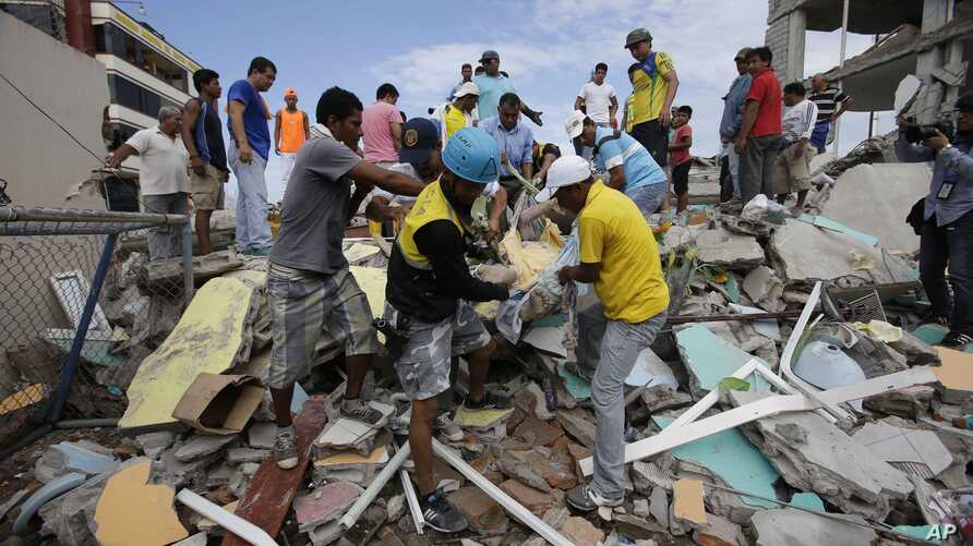 Volunteers rescue a body from a destroyed house after a massive earthquake in Pedernales, Ecuador, April 17, 2016.