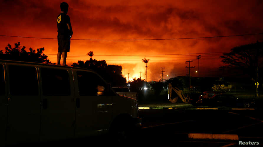 Darryl Sumiki, 52, of Hilo, watches as lava lights up the sky above Pahoa during ongoing eruptions of the Kilauea Volcano in Hawaii, U.S., June 2, 2018.