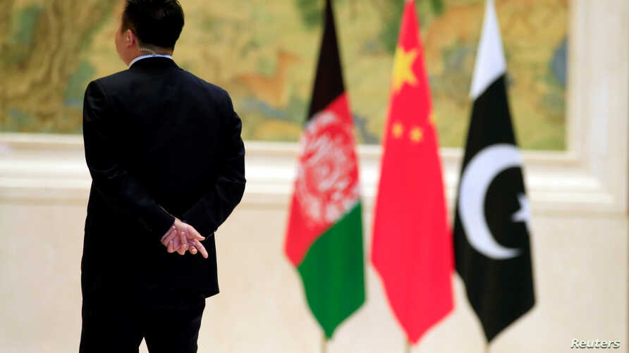FILE - A security worker stands near, from left, Afghan, Chinese and Pakistani flags during the 1st China-Afghanistan-Pakistan Foreign Ministers Dialogue in Beijing, Dec. 26, 2017. China, Afghanistan and Pakistan over the past two years also have lau