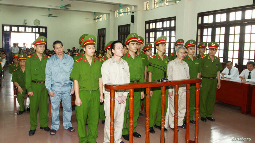 Doan Van Vuon (standing, 4th L), Doan Van Quy (standing, 2nd L) and Doan Van Sinh (standing, 3rd R) stand with policemen in front of the dock at a court during a verdict session in Hai Phong, April 5, 2013, in this picture provided by the Vietnam New