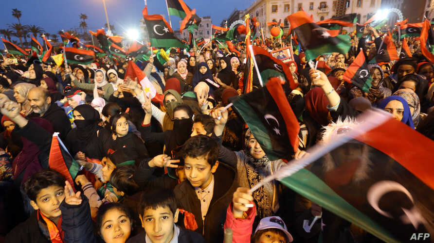 Libyans wave national flags as they attend a celebration marking the seventh anniversary of the Libyan revolution which toppled late leader and strongman Moamer Kadhafi, in the capital Tripoli's Martyrs Square, Feb. 17, 2018.