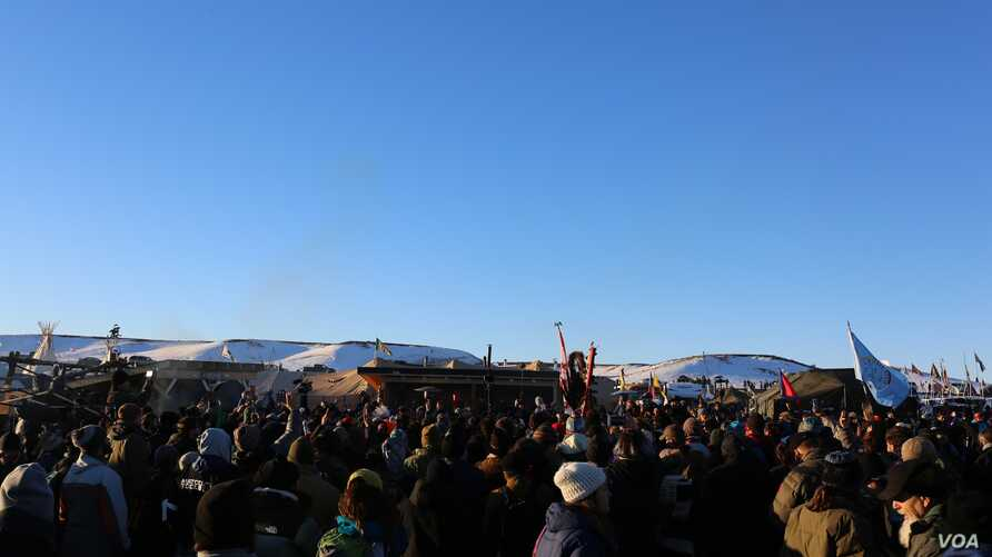 Water protectors celebrate the decision of the Army Corps to deny the building of the Dakota Access Oil Pipeline through their and sacred Sioux land (E. Sarai/VOA)