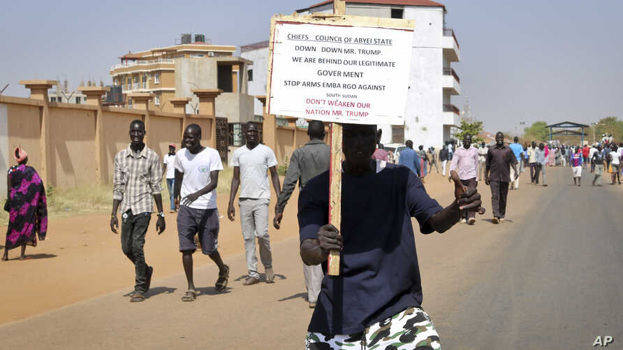 A demonstrator holds a placard during a rally protesting the United States' unilateral arms embargo on the country, in Juba, South Sudan, Feb. 6, 2018.