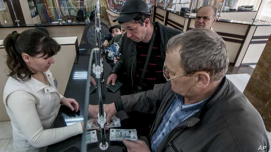 Crimean retirees line up to get their pensions in Russian rubles inside a post office in Simferopol, Crimea, Tuesday, March 25, 2014. The Crimean authorities began paying pensions in rubles following the Ukrainian region's annexation by Russia. (AP P