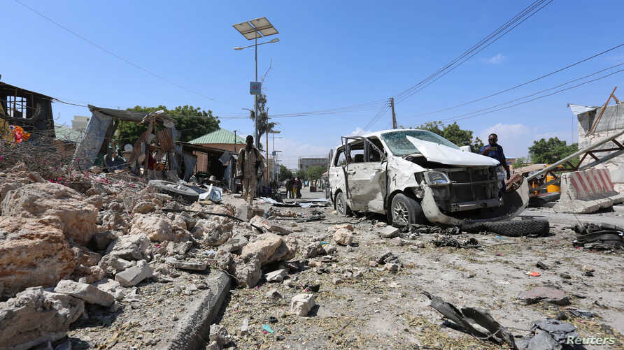 Somali policemen look at the wreckage of a destroyed car at the scene of a suicide attack at a checkpoint outside the main base of an African Union peacekeeping force in the Somali capital Mogadishu, Jan. 2, 2017.
