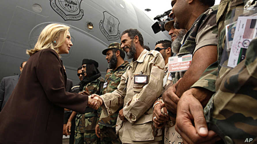US Secretary of State Hillary Rodham Clinton meets Libyan soldiers at the steps of her C-17 military transport upon her arrival in Tripoli in Libya, October 18, 2011.