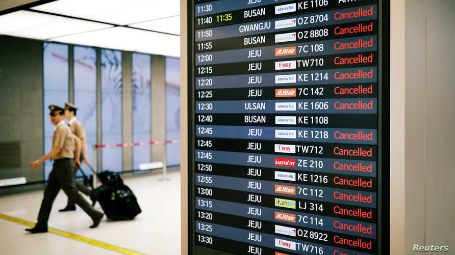 Pilots walk past an electronic board that shows canceled domestic flights because of Typhoon Soulik at Gimpo airport in Seoul, South Korea, Aug. 23, 2018.