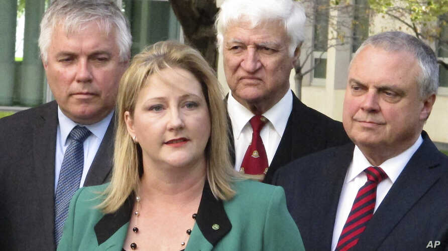 Independent Australian lawmaker Rebekha Sharkie, second left, announces her resignation to reporters at Parliament House in Canberra, Australia, Wednesday, May 9, 2018.