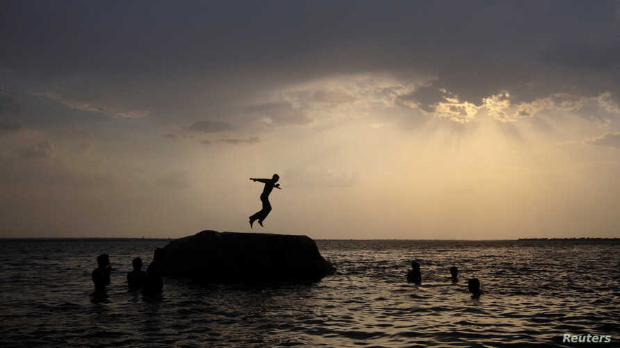 A boy prepares to jump off a rock into the waters of the Osman Sagar Lake near the southern Indian city of Hyderabad, May 29, 2011.