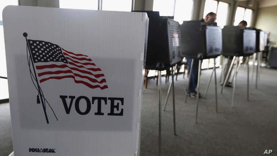 FILE - Voters cast ballots in Hinsdale, Ill., March 18, 2014.