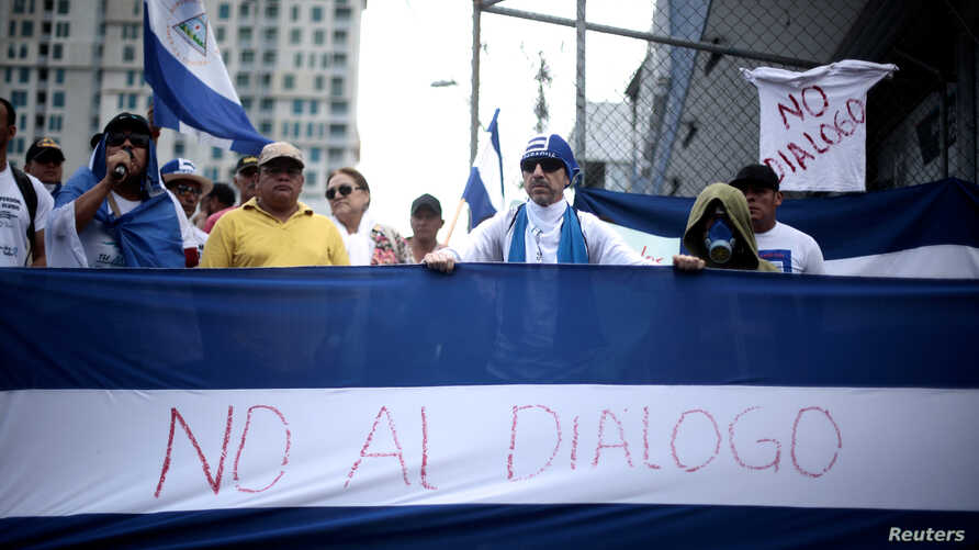 "Nicaraguans display a national flag saying ""No to dialogue"" during a protest in San Jose, Costa Rica, against the talks their President Daniel Ortega will resume with the leaders of the opposition, Feb. 22, 2019."
