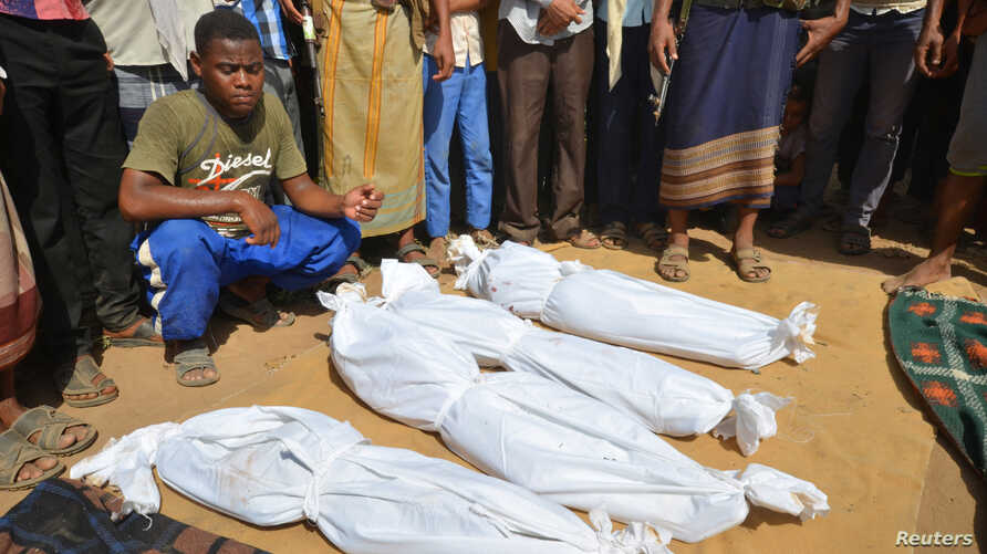 A man sits as others stand near the wrapped up bodies of children from the same family, one day after they were killed in a Saudi-led airstrike on their house in Bajil district of the Red Sea province of Houdieda, Yemen, Oct. 8, 2016.
