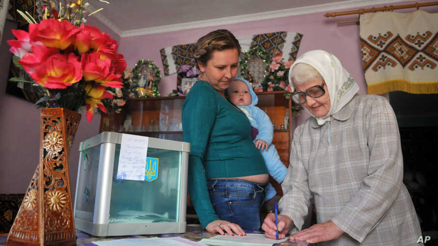 An elderly woman fills in the ballot while a woman with a child watches, as they vote at home in the village of Stilske, west Ukraine on Sunday, Oct. 25, 2015.