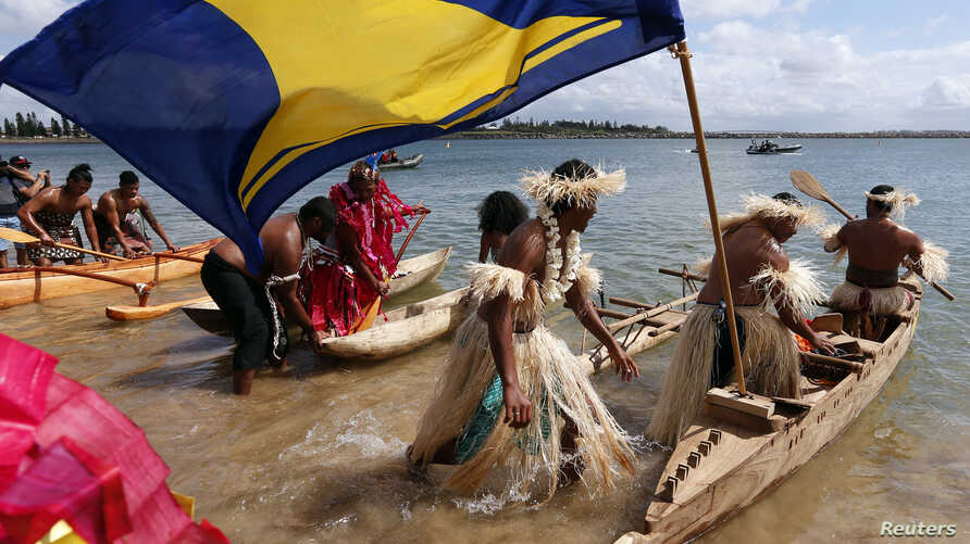 Traditionally-dressed representatives from South Pacific nations push their canoes into the water as they prepare to participate in a protest aimed at ships leaving the Newcastle coal port, located north of Sydney, Australia, Oct. 17, 2014.