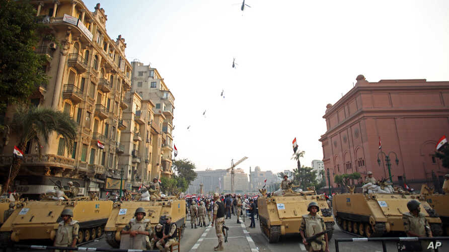 FILE - Egyptian military helicopters fly overhead as army soldiers stand guard at an entrance to Tahrir Square, in Cairo, Egypt, Oct. 6, 2013. The United States on July 26, 2018, released $195 million in military aid to Egypt that had been withheld b