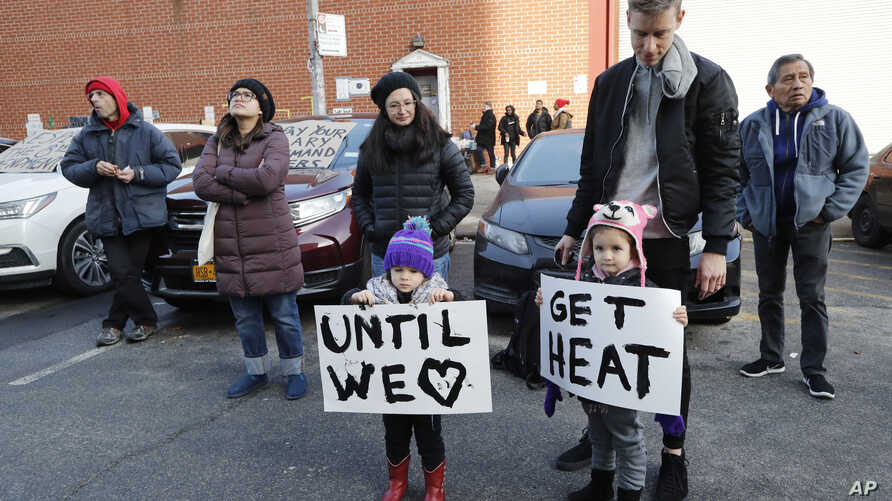 Reina Benn, 3, and her twin sister Chiara hold signs as their father, Michael Benn, second from right, keeps an eye on them as they joined other protesters and prisoners' family members at a vigil outside the Metropolitan Detention Center, Feb. 3, 20