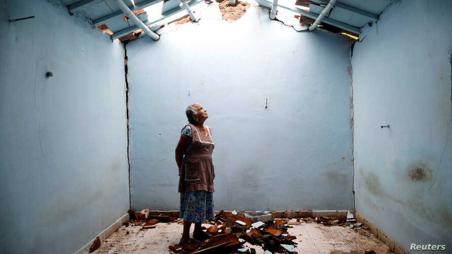 FILE - Tomasa Mozo, 69, a housewife, looks up at the roof inside the ruins of her house after an earthquake in San Jose Platanar, at the epicentre zone, Mexico, Sept. 28, 2017.