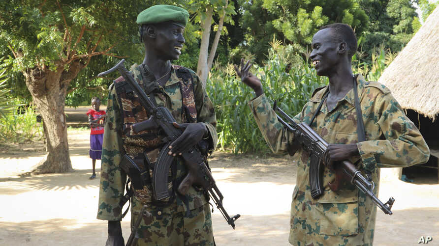In this photo taken Wednesday, Aug. 15, 2018, two opposition soldiers talk together outside their base in the opposition-held town of Nyal in Unity state, in South Sudan.