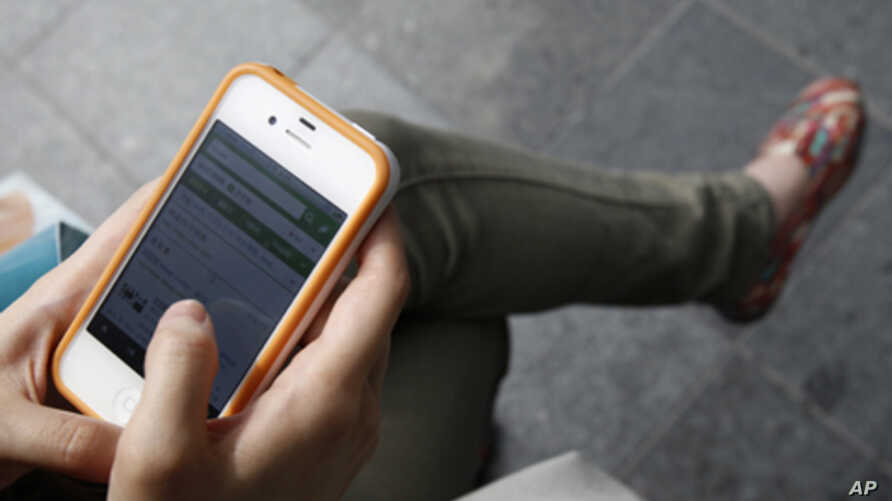 A woman uses her Apple iPhone 4 smartphone (file photo)