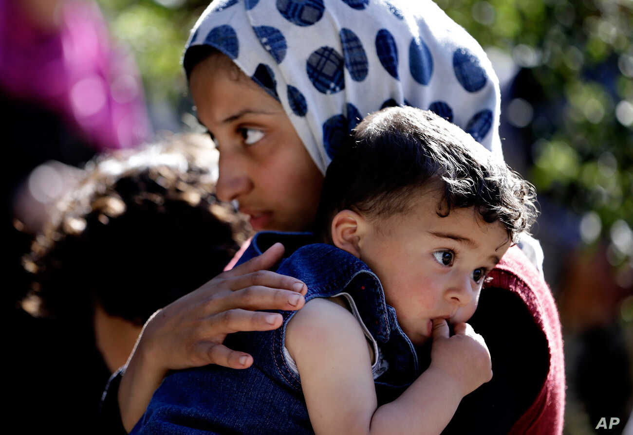 A Syrian refugee carries her sister in Ketermaya village southeast of Beirut, Lebanon, March 14, 2013.