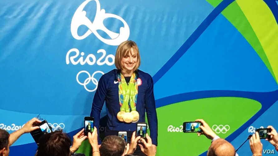U.S. swimmer Katie Ledecky poses with her medals after her final news conference at the Rio Olympics Main press center, Rio de Janeiro, Aug. 13, 2016. (P. Brewer/VOA)
