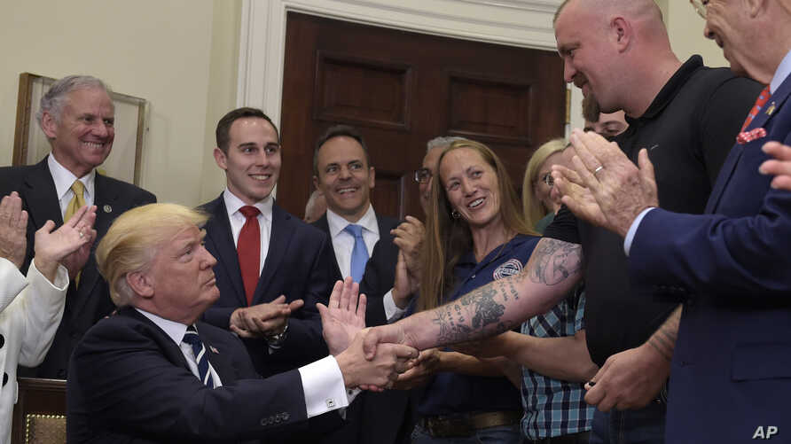 President Donald Trump shakes hands with Charles Robel after signing an executive in the Roosevelt Room of the White House in Washington, June 15, 2017, during an event on Apprenticeship and Workforce of Tomorrow initiatives.