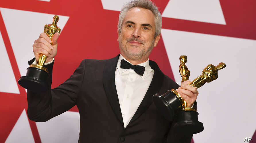 "FILE - Alfonso Cuaron poses with the awards for best director for ""Roma,"" best foreign language film for ""Roma,"" and best cinematography for ""Roma"" in the press room at the Oscars at the Dolby Theatre in Los Angeles, Feb. 24, 2019."