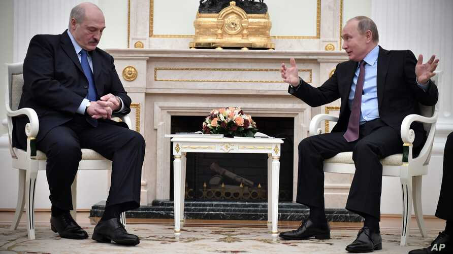 Russian President Vladimir Putin, right, gestures as he speaks to his Belarusian counterpart Alexander Lukashenko, foreground left, during their talks in the Kremlin in Moscow, Russia, Tuesday, Dec. 25, 2018.