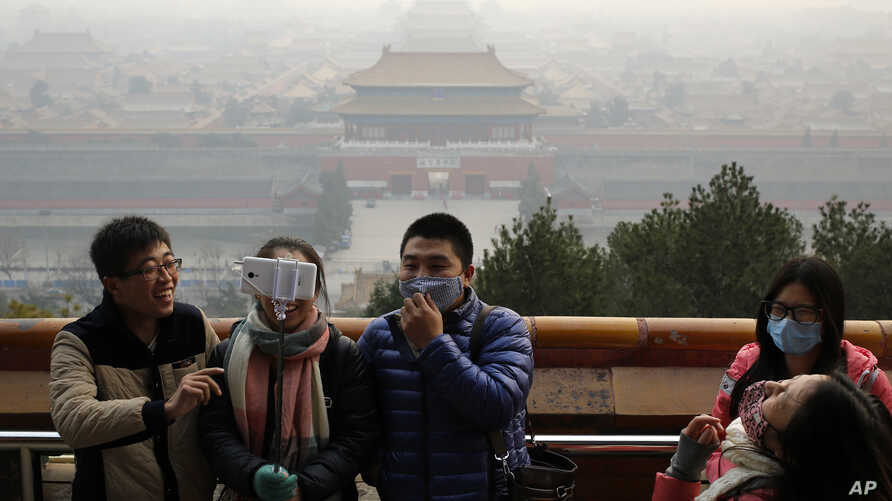 Visitors, some wearing masks to protect themselves from pollutants, share a light moment as they take a selfie at the Jingshan Park on a polluted day in Beijing, Monday, Dec. 7, 2015. Smog shrouded the capital city Monday after authorities in Beijing
