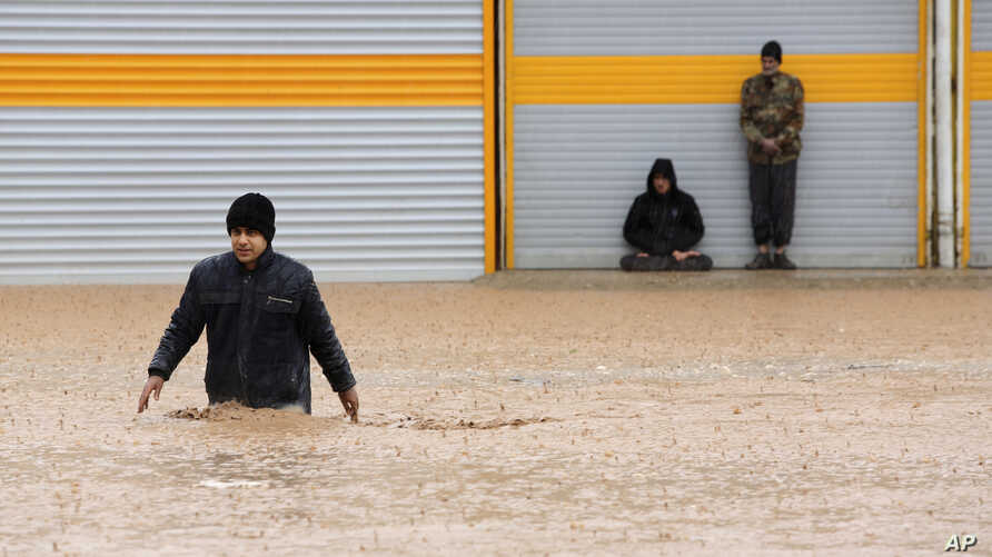 A man crosses a flooded street in the city of Khorramabad in western province of Lorestan, Iran, April 1, 2019.