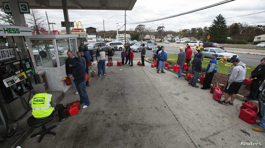 People affected by the power outages from Hurricane Sandy wait in a 2hr line at a gas station to purchase fuel for generators in Madison Park, New Jersey, October 31, 2012.