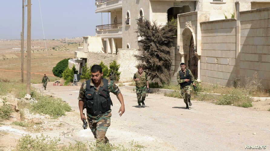 Forces loyal to Syria's President Bashar al-Assad carry their weapons as they move during what they said a military operation against rebels in al-Mansoura, in the Aleppo countryside, June 3, 2013.