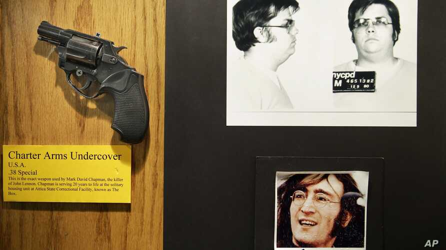 FILE - The gun used by Mark David Chapman to kill John Lennon is displayed next to their pictures at a small museum in the Forensic Investigation Division of the New York Police Department in New York, Dec. 8, 2015.