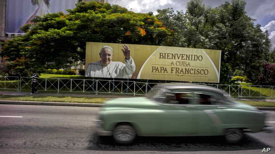 """A man drives a vintage American car next to a display — which reads """"Welcome to Cuba Pope Francis"""" in Spanish — at Revolution Square in Havana, Cuba, Sept. 15, 2015."""