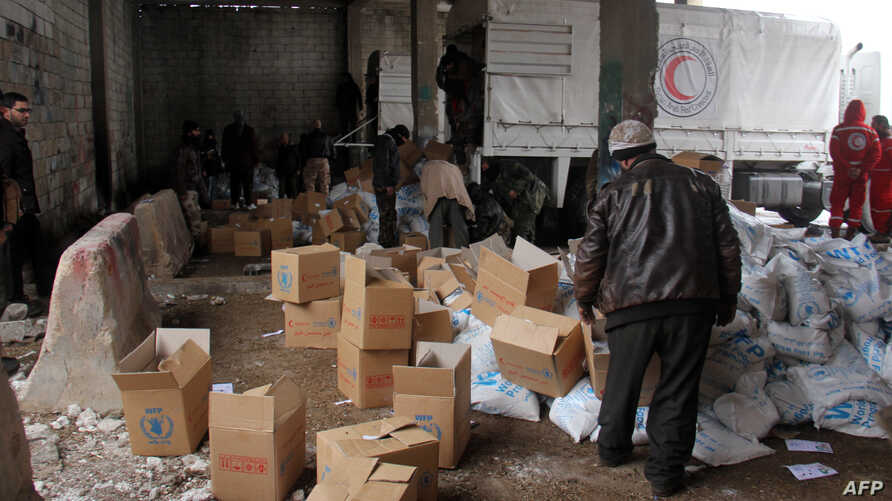 FILE - Aid parcels and boxes are offloaded from vehicles in a warehouse in Idlib, in northwestern Syria.