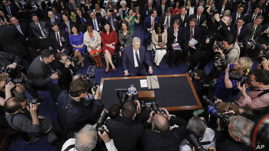 Supreme Court nominee Neil Gorsuch arrives and takes his seat on Capitol Hill in Washington for his confirmation hearing before the Senate Judiciary Committee, March 20, 2017.