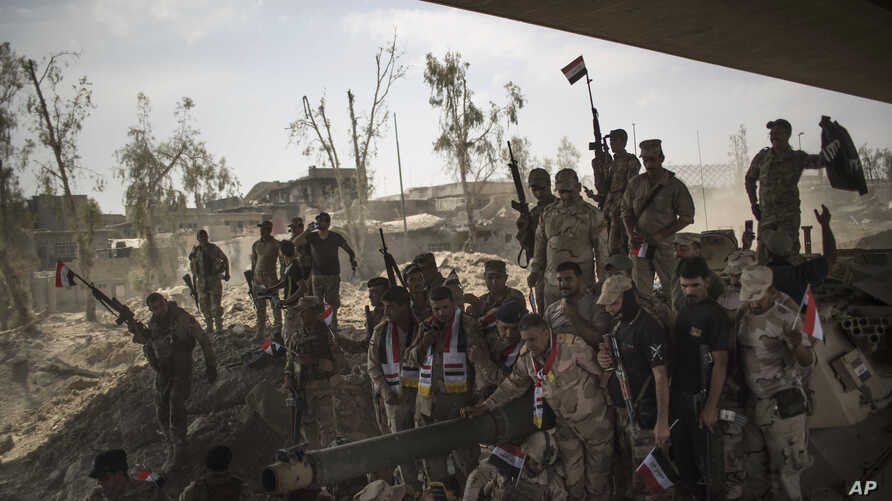 Iraqi Army soldiers gather to celebrate their gains as their fight against Islamic State militants continues in the Old City of Mosul, Iraq, July 9, 2017.