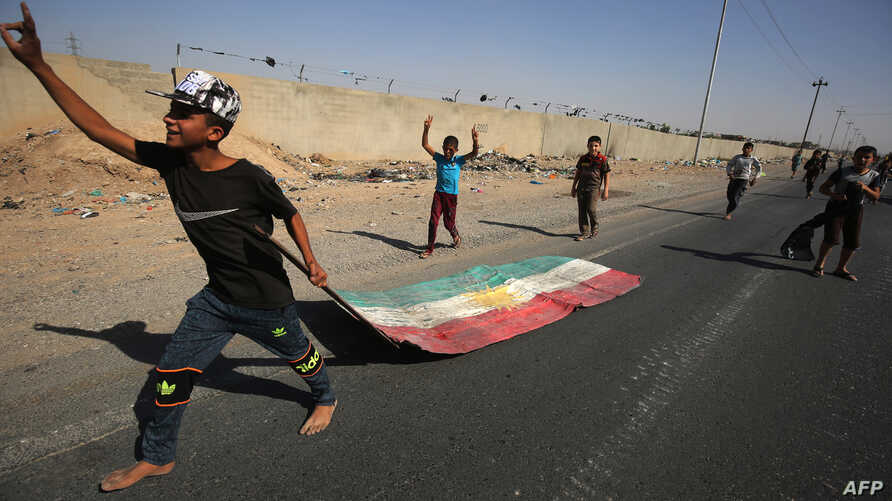 An Iraqi boy drags a Kurdish flag as Iraqi forces advance towards the center of Kirkuk during an operation against Kurdish fighters on Oct. 16, 2017.