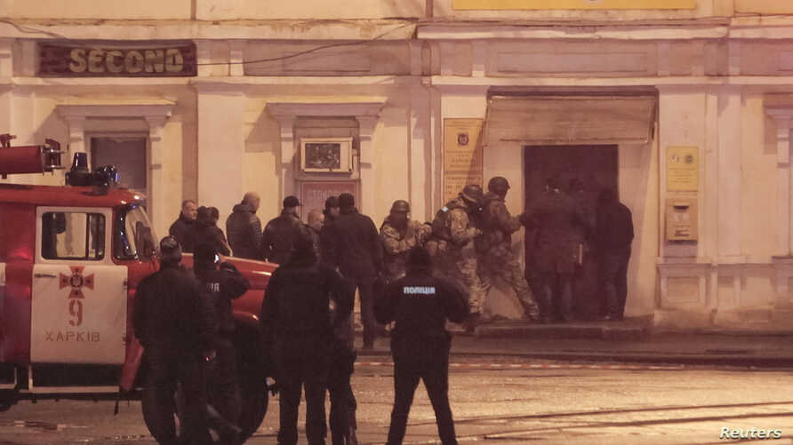Members of a police special operations unit gather outside a post office, where a man took people hostage, in Kharkiv, Ukraine, Dec. 30, 2017.