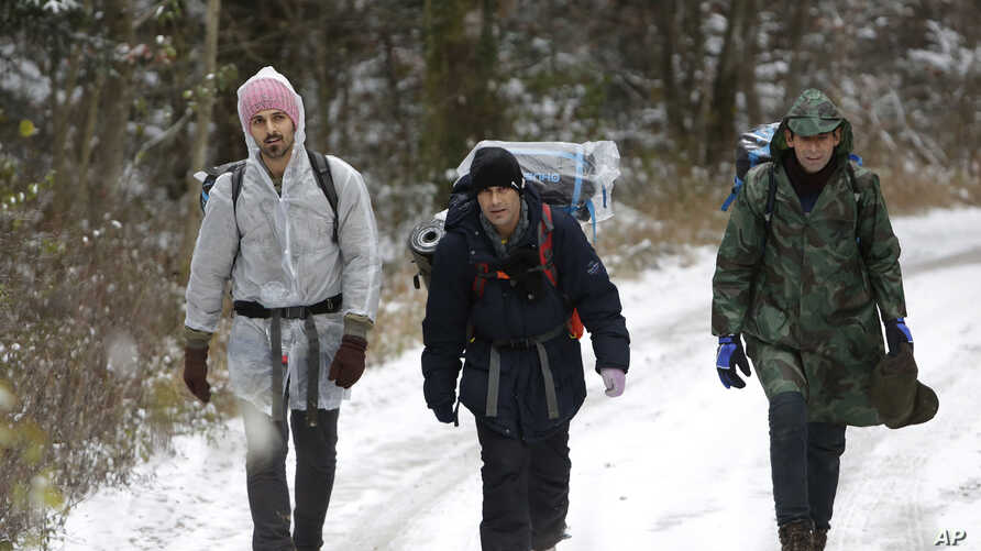 A group of migrants moves through a forest on the Pljesevica Mountain in a attempt to illegally cross the border into Croatia, in Bihac, Bosnia, Nov. 28, 2018.