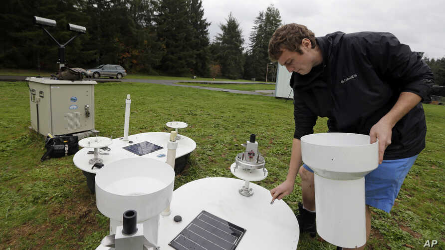 Brandon Jameson, a ground validation engineer, adjusts a rain gauge located at the Quinault National Fish Hatchery, near Humptulips, Wash., Nov. 6, 2015.